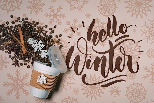 Vista superior de granos de café y hola letras de invierno