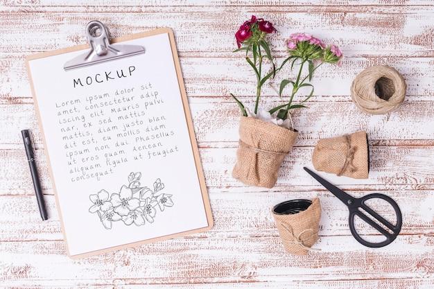 Vista superior de herramientas de jardinería y flores con maqueta de portapapeles