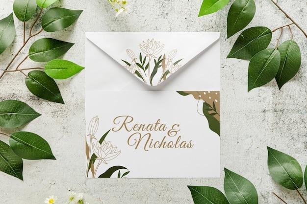 Vista superior invitación de boda con hojas