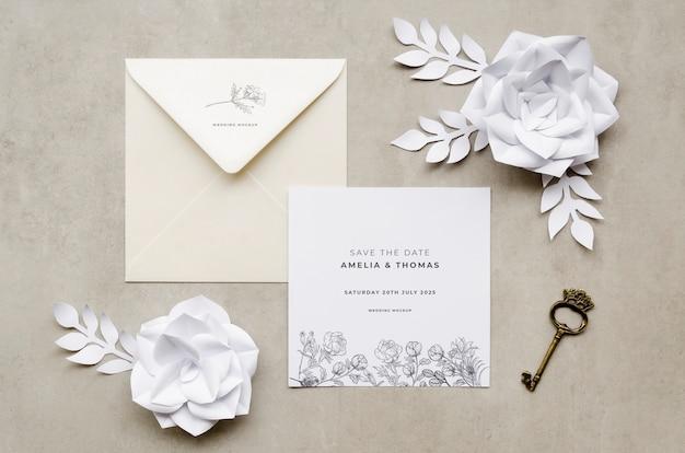 Vista superior de la invitación de boda con rosas de papel y llave