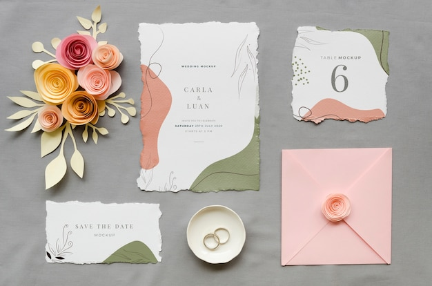 Vista superior de invitaciones de boda con rosas y anillos