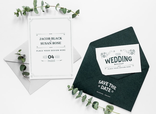 Vista superior de invitaciones de boda con sobre y plantas