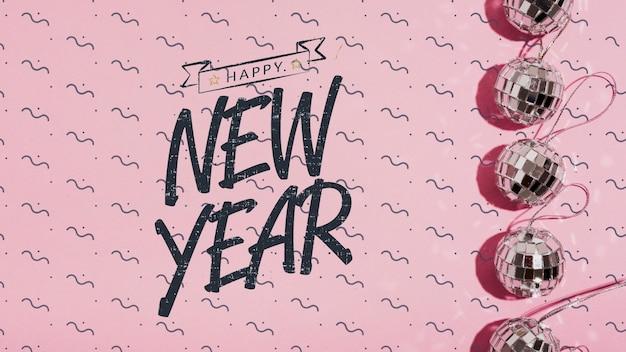 Vista superior letras de año nuevo con pequeños adornos de bolas de discoteca