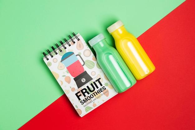 Vista superior libreta y botellas con batido de frutas