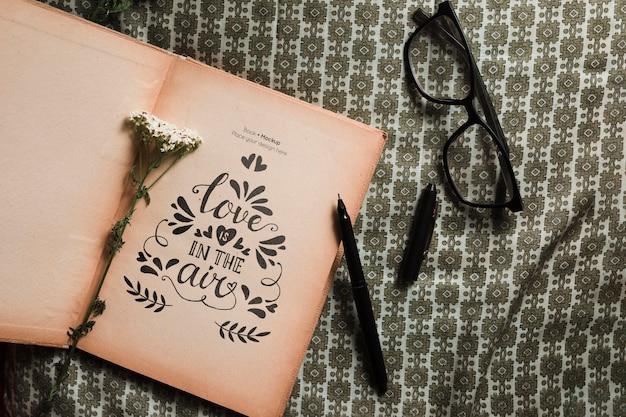Vista superior del libro con gafas y bolígrafo