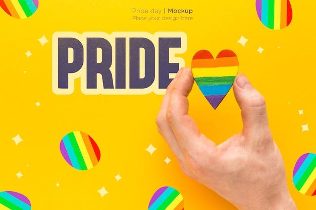 Vista superior de la mano que sostiene el corazón de color del arco iris por orgullo