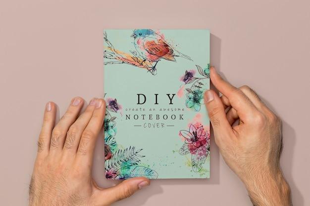Vista superior de las manos en la maqueta del libro