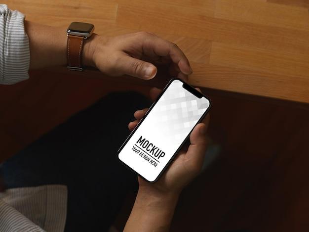 Vista superior de manos masculinas con smartphone mientras está sentado en la sala de la oficina