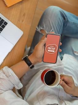 Vista superior de manos sosteniendo smartphone de maqueta