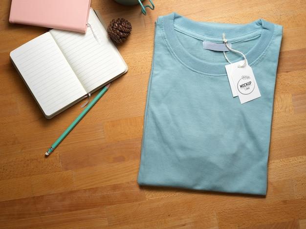 Vista superior de la maqueta de camiseta azul con etiqueta de precio de maqueta en la mesa de estudio de madera