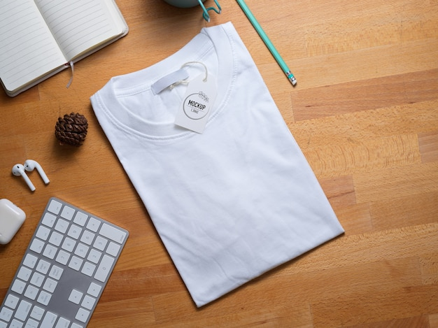 Vista superior de la maqueta de camiseta blanca con etiqueta de precio en la mesa de trabajo de madera con suministros