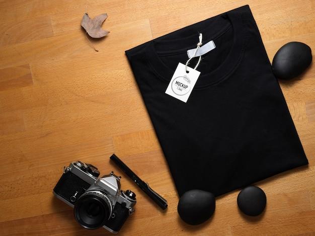 Vista superior de maqueta camiseta negra con etiqueta de precio en mesa de madera con cámara