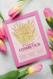 Vista superior maqueta de cosméticos con flores.