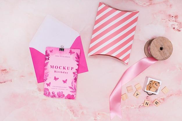 Vista superior de la maqueta de regalo de cumpleaños con tarjeta y sobre