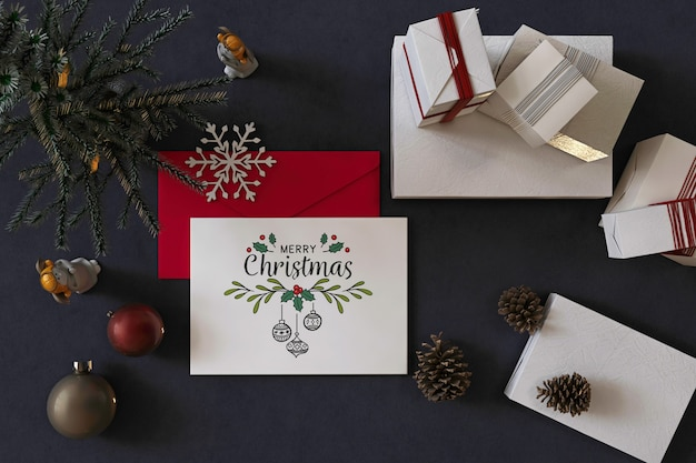 Vista superior maqueta de tarjeta de felicitación de feliz navidad con decoración navideña, sobre rojo y regalos