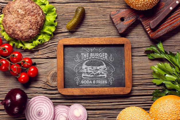 Vista superior marco hamburguesa ingredientes fondo madera