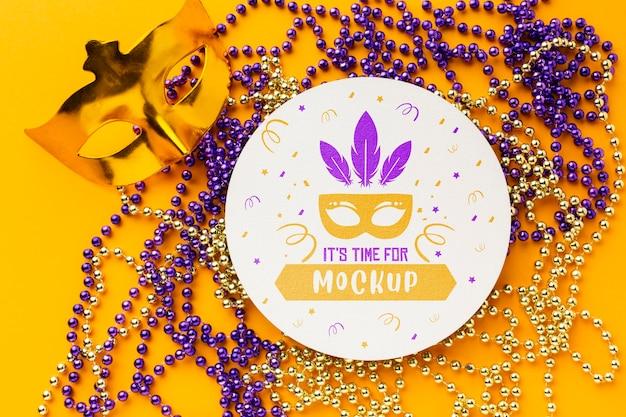 Vista superior de la máscara de carnaval y perlas.