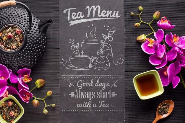 Vista superior de menú de té con hierbas y flores.