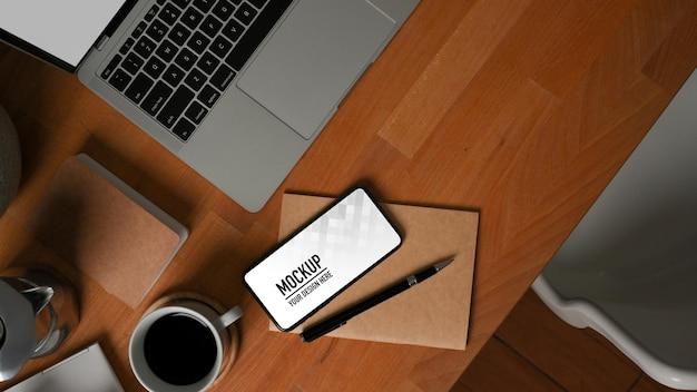 Vista superior de la mesa de madera con teléfono inteligente, maqueta de computadora portátil