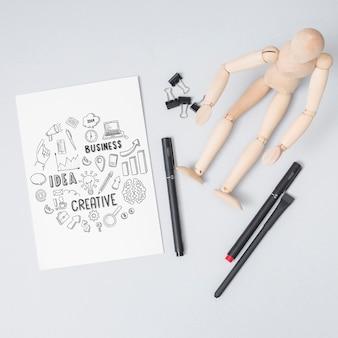 Vista superior muñeca de madera con bolígrafos
