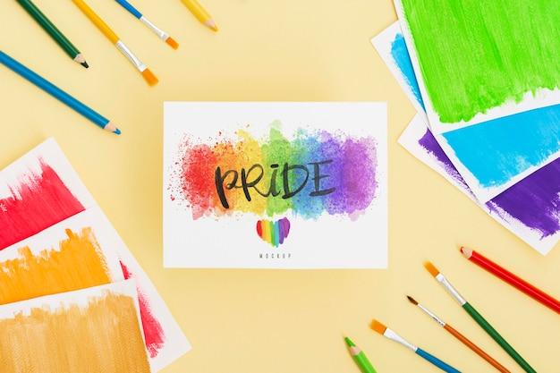 Vista superior de papeles de colores del arco iris con pinceles y lápices para orgullo lgbt