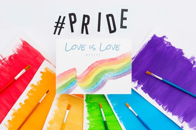 Vista superior de papeles de colores arcoíris con pinceles para orgullo lgbt