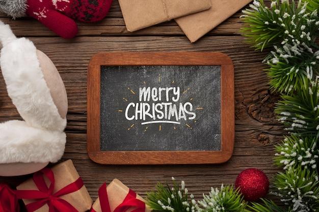 Vista superior pizarra de feliz navidad y hojas de pino de navidad
