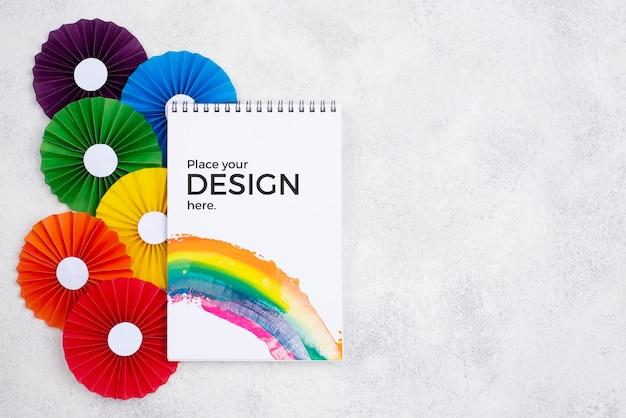 Vista superior de rosetas de colores del arco iris y cuaderno
