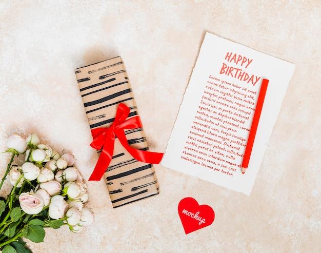 Vista superior saludo de cumpleaños con regalo y flores