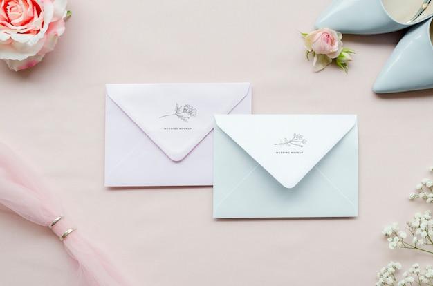Vista superior de sobres de boda con zapatos y anillos
