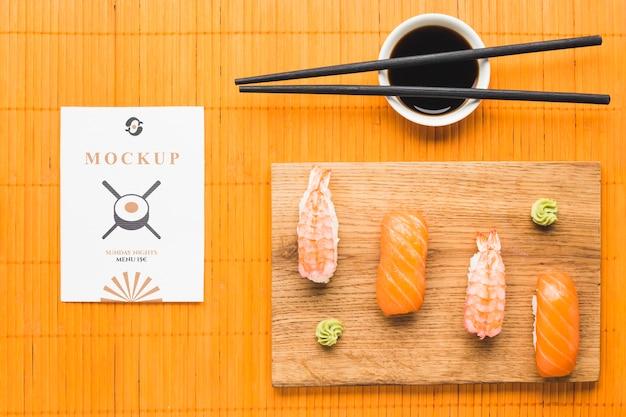Vista superior de sushi en una tabla de cortar con salsa de soja y palillos