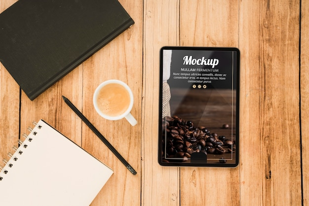 Vista superior de la tableta con taza de café y cuaderno