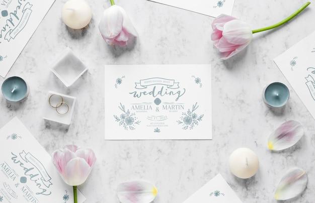 Vista superior de la tarjeta de boda con anillos y tulipanes
