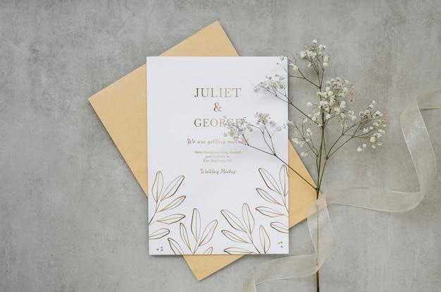 Vista superior de la tarjeta de boda con flores y cinta