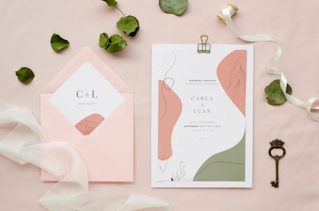 Vista superior de la tarjeta de boda con hojas y llave