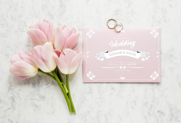 Vista superior de la tarjeta de boda con ramo de tulipanes y anillos