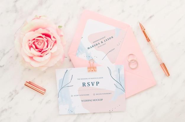Vista superior de la tarjeta de boda con rosa y bolígrafo