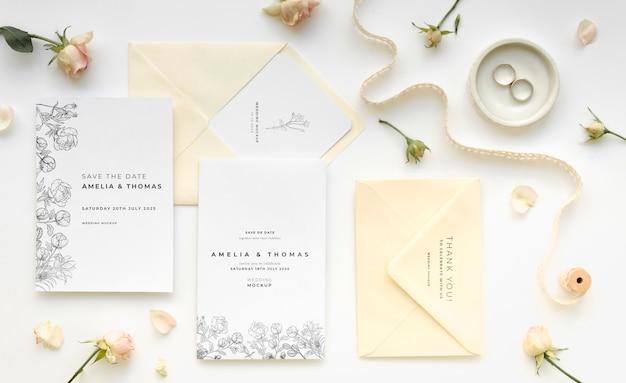 Vista superior de tarjetas de boda con anillos y flores.