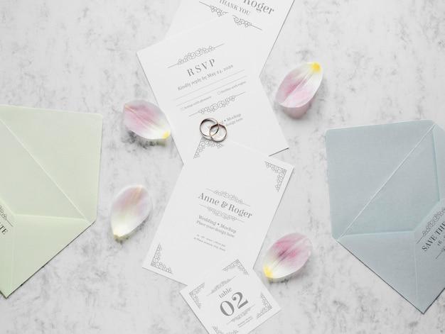 Vista superior de tarjetas de boda con anillos y pétalos de flores