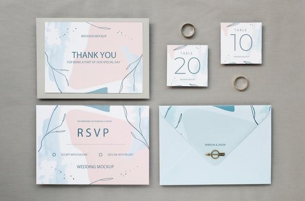 Vista superior de tarjetas de boda con anillos y sobres
