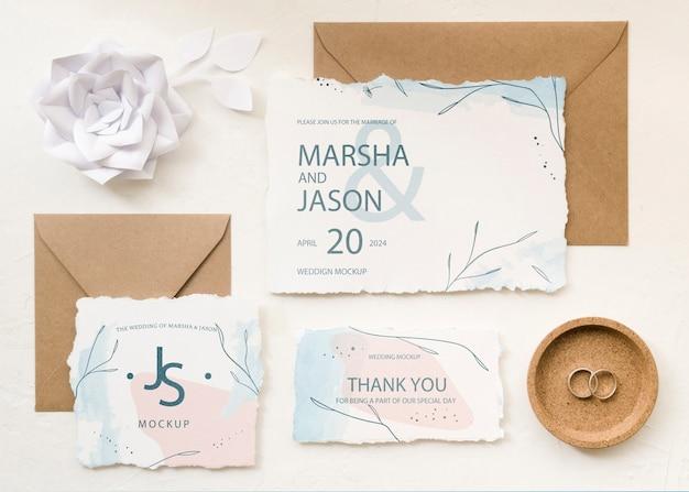 Vista superior de tarjetas de boda con rosa de papel y anillos