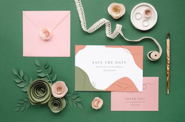 Vista superior de tarjetas de boda con rosas de papel y bolígrafo
