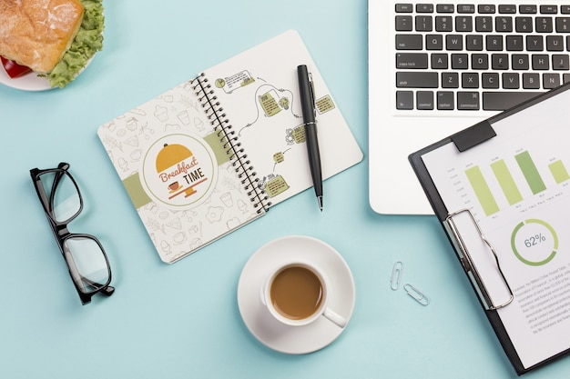 Vista superior taza de café con anteojos en el escritorio