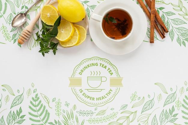 Vista superior taza de té con limones