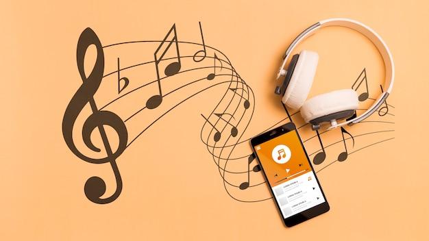 Vista superior del teléfono inteligente con auriculares y notas musicales