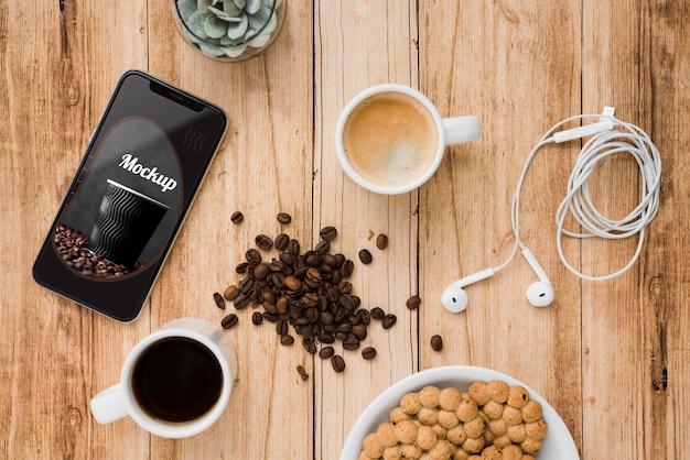 Vista superior del teléfono inteligente con granos de café y taza de té