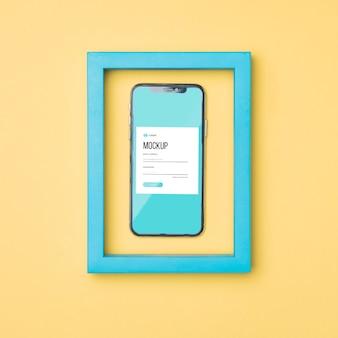 Vista superior del teléfono inteligente en una maqueta de marco azul