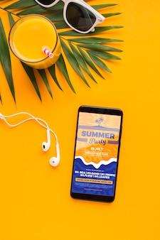 Vista superior del teléfono móvil con auriculares y jugo de naranja