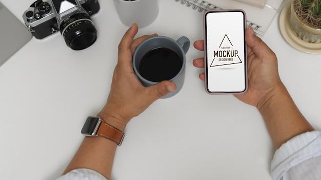 Vista superior del trabajador de oficina masculino que usa un teléfono inteligente simulado mientras toma un café en la mesa de trabajo