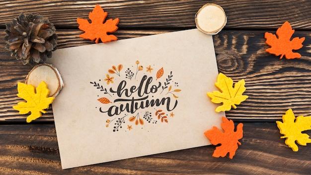 Vista superiore della carta di autunno di ciao sulla tavola di legno